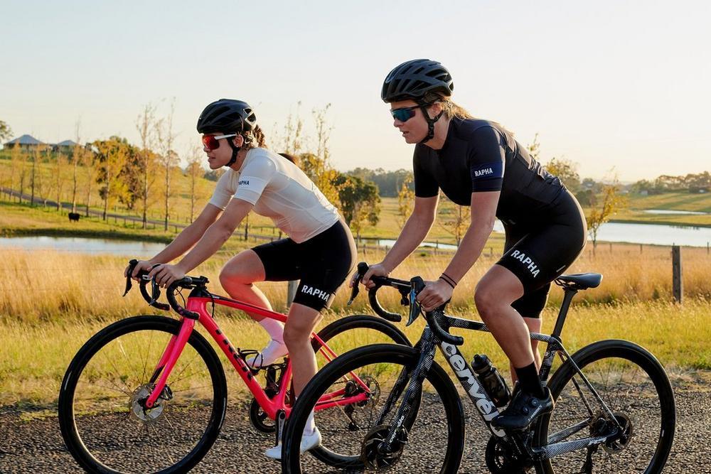 two women riding bikes in rapha gear